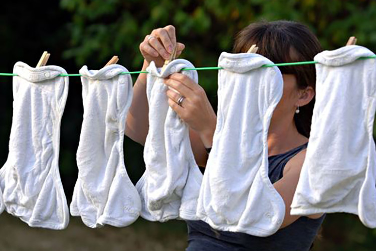 A lady hanging up cloth nappies on a washing line